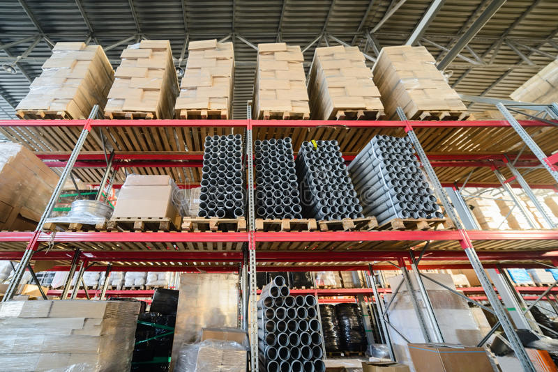 Long shelves with a variety of boxes and containers. Warehouse industrial goods. Large long racks. Cardboard boxes and coiled plastic tube. Toning the image stock photo