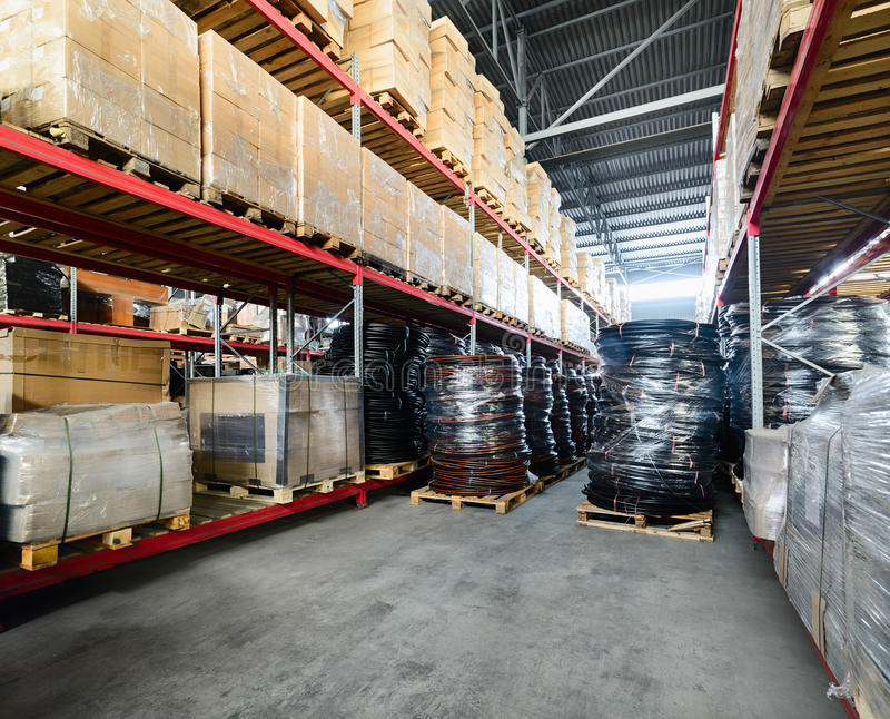 Long shelves with a variety of boxes and containers. Warehouse industrial goods. Large long racks. Cardboard boxes and coiled plastic tube. Toning the image stock photography