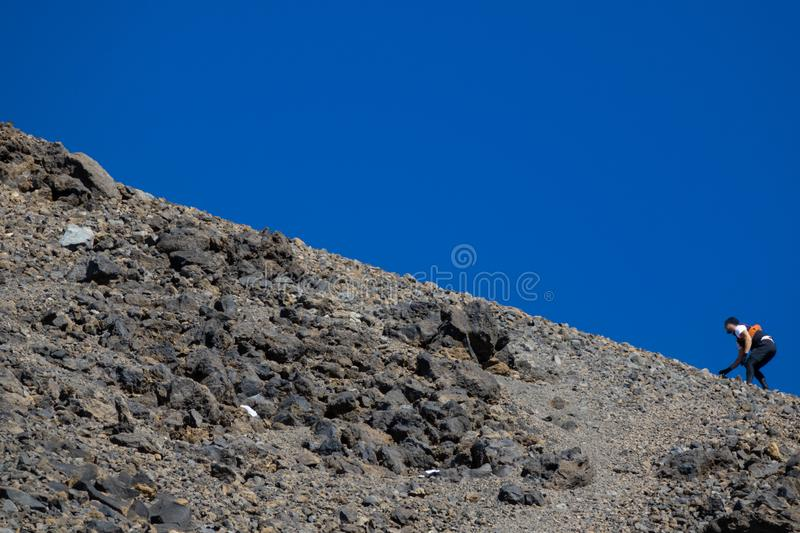 Blurred runner climbing difficult slope against blue sky royalty free stock images