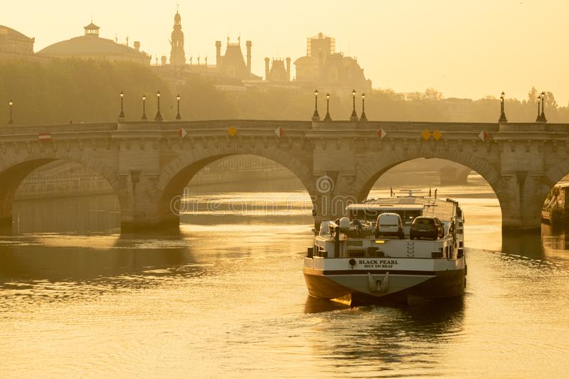 Long shot of a cargo barge passing under the Pont Neuf in Paris during dawn twilight stock photography