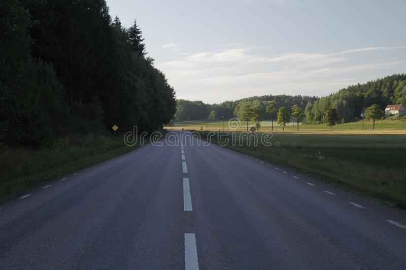 Long shot of an empty road with trees and greenery on the side of the road. A long shot of an empty road with trees and greenery on the side of the road stock photography