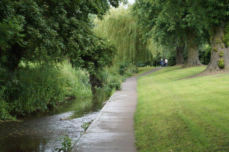 Long shot of trees and stream. An idyllic scene with grass verge, foliage, pathway and flowing water. Two dog walkers in the distance of this scenic view stock photos
