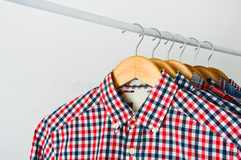 Long sleeve red and blue checkered shirt on wooden hanger over white background stock photos