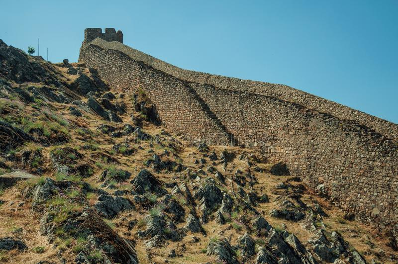 Long solid wall made of stone rising along the hill stock images