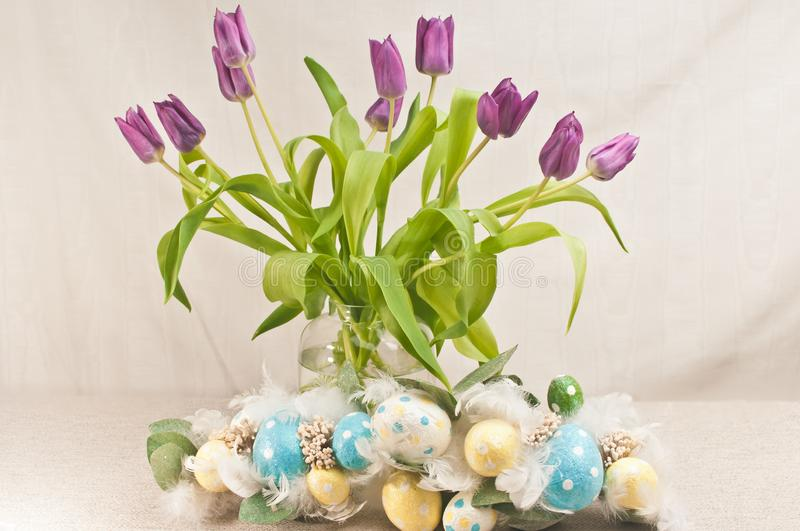 Long stemmed, purple, tulips and colored easter eggs royalty free stock photos