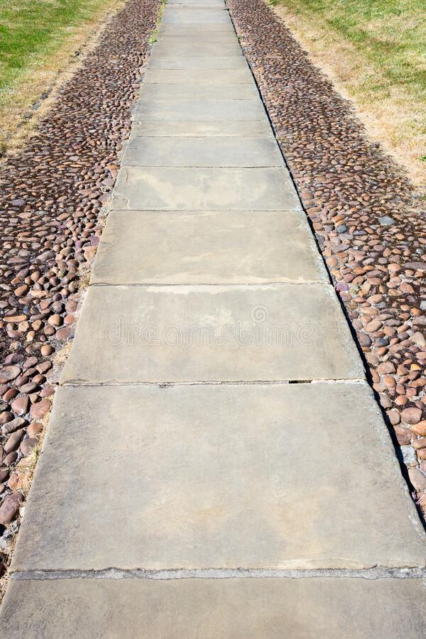 Long stone foot path with stone cobbles. On either side stock photography