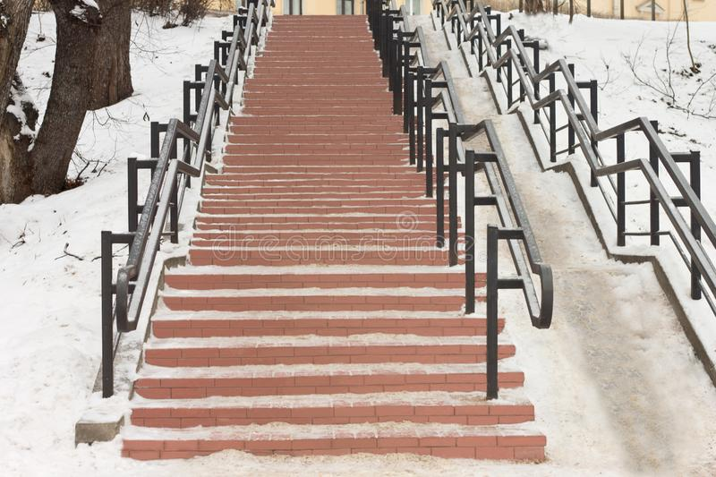 In the center of the city in the park there is a stone staircase with iron railing. Long stone staircase with iron railings in a city park stock photos