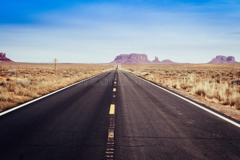 Long straight american road with vanishing point into Monument Valley stock images