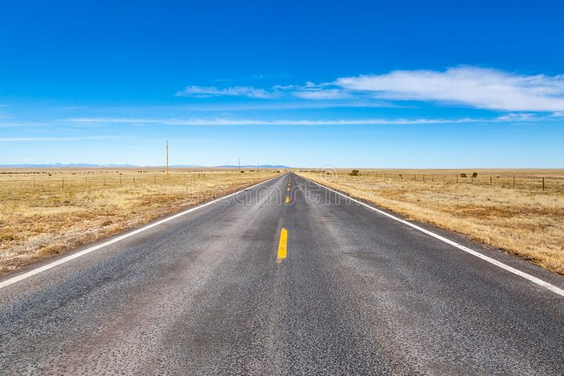 A Road in New Mexico. A long, straight road in rural New Mexico, with a blue sky overhead stock image