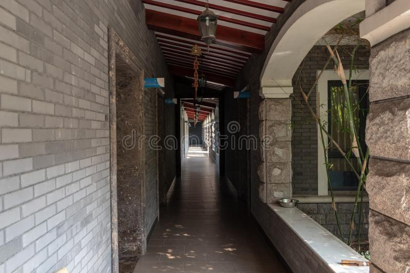 Long summer corridor of the building with open doors. Stone tiled floor, open windows. Hanging Chinese lanterns. stock image