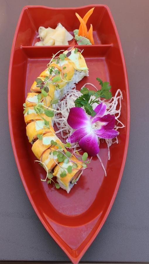 Long sushi roll filled with the freshest ingredients covered in mango slices. Large platter with sliced sushi roll filled with the freshest seafood ingredients royalty free stock photo
