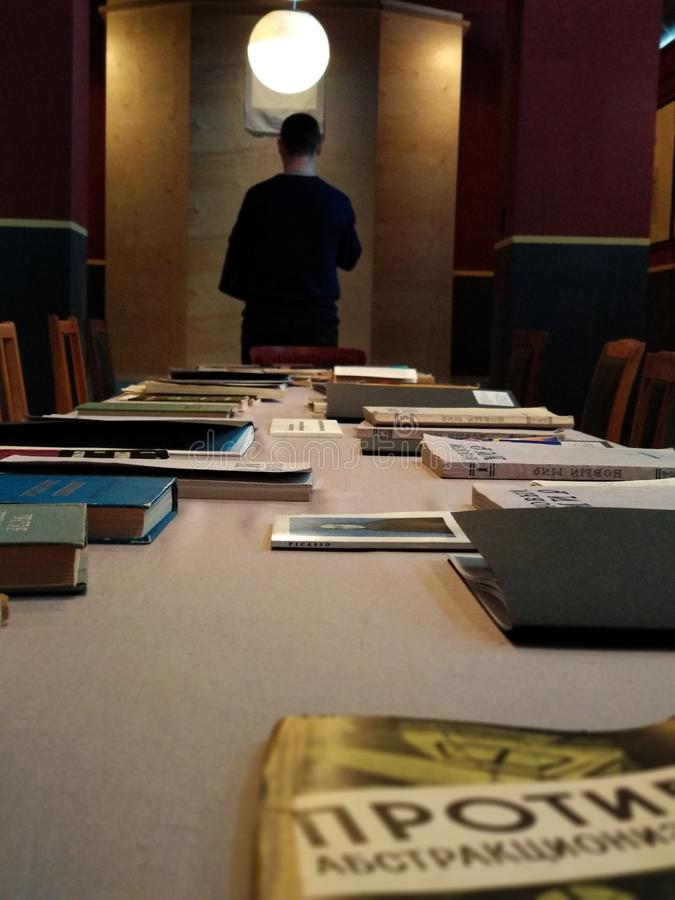 Long table with books and a man standing back in the background royalty free stock images