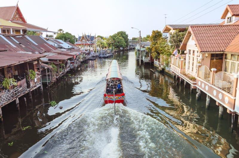 The long tail boat at Bangkok yai canal or Khlong Bang Luang. The long tail boat cruising through WATKHUHASAWAN TEMPLES at Bangkok yai canal or Khlong Bang Luang royalty free stock photos