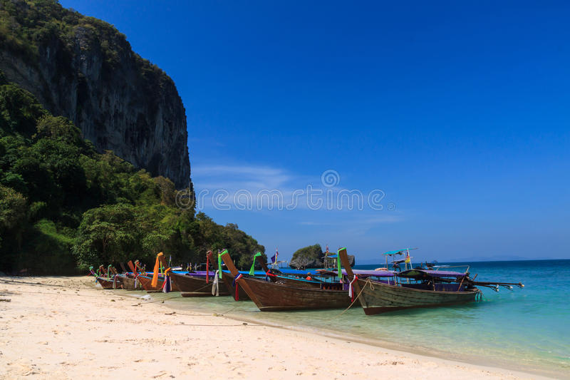 Long tail boat in front of the beach stock images