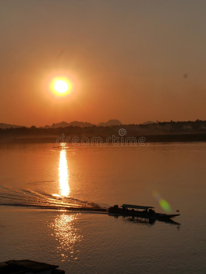 Long tail boat on a river during sunset. Long tail boat driving on a calm steady peaceful river during sunset on orange sky and sun reflection stock images