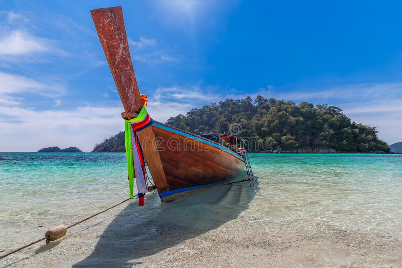 Long tail boat on white sand beach on tropical island in thailand royalty free stock images