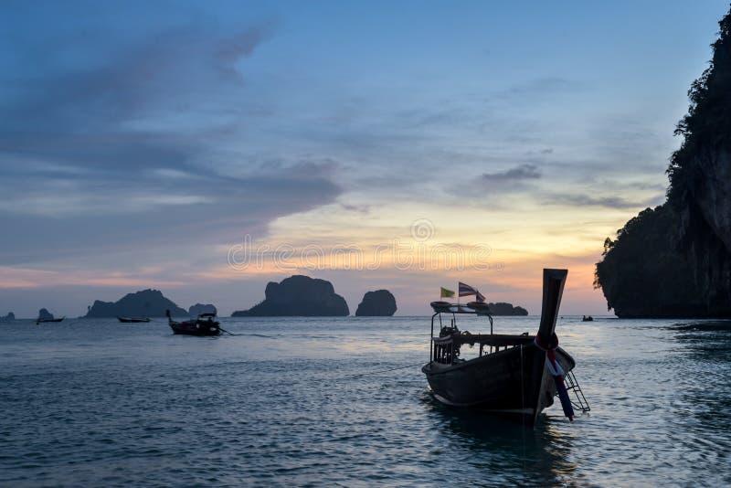 Long tail boats at Sunset at Ko Rang Nok Island in Ao Phra Nang beach, Krabi. Long tail traditional boats a peaceful evening sunset at Ko Rang Nok island in Phra royalty free stock photos
