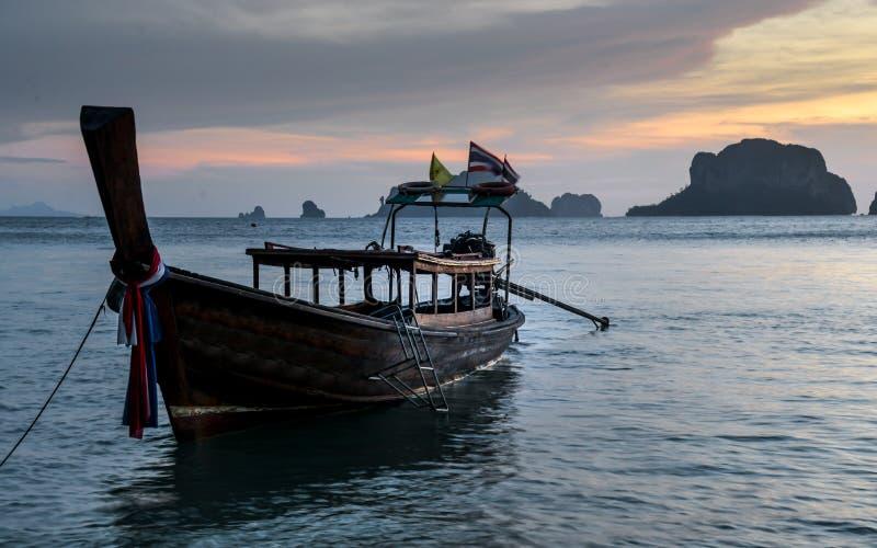 Long tail boats at Sunset at Ko Rang Nok Island in Ao Phra Nang beach, Krabi. Long tail traditional boats a peaceful evening sunset at Ko Rang Nok island in Phra royalty free stock photography
