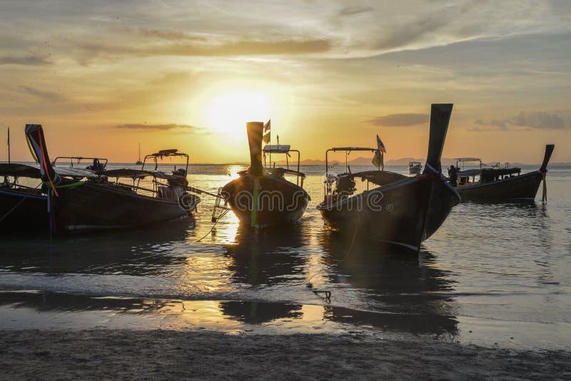 Long tail boats at Sunset at Ko Rang Nok Island in Ao Phra Nang beach, Krabi. Long tail traditional boats a peaceful evening sunset in Phra Nang Beach Cave royalty free stock images