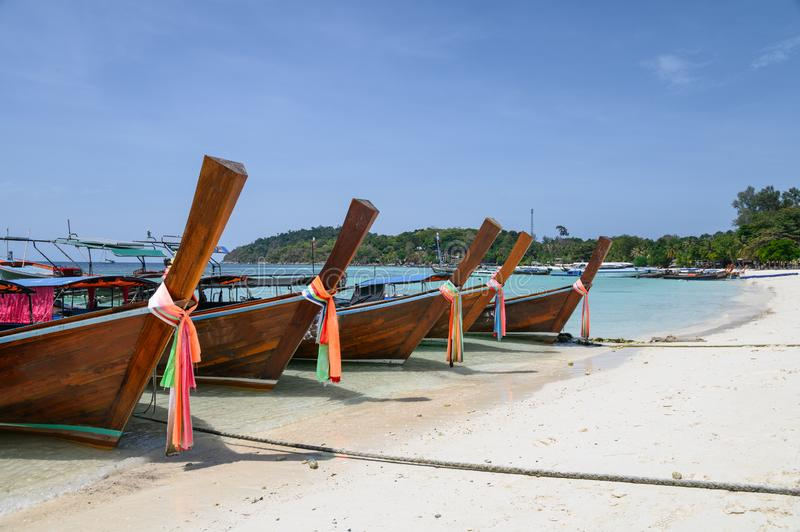 Long-tail wooden boats anchored on white beach in tropical sea. At lipe island stock photography