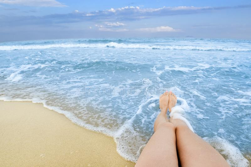 Long tanned girl legs against background of endless blue sea water royalty free stock image