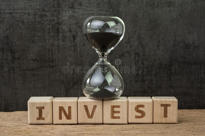 Long term investment, countdown to crisis or stock market timing concept, sandglass or hourglass on wooden cube block with royalty free stock images