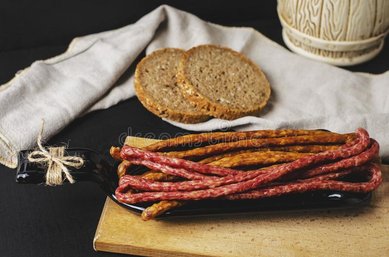 Long thin smoked sausages and slices of bread on black background on a plate made from bottle. royalty free stock photos