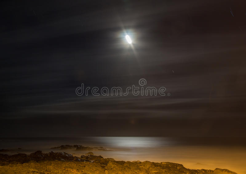 Long time exposure at night of the moon over the Wild Coast at t. He Indian Ocean in South Africa during summertime stock image