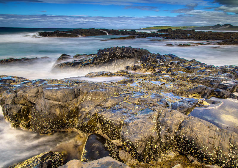 Long time exposure of waves around rocks at the Wild Coast at th. E Indian Ocean in South Africa during summertime royalty free stock photo