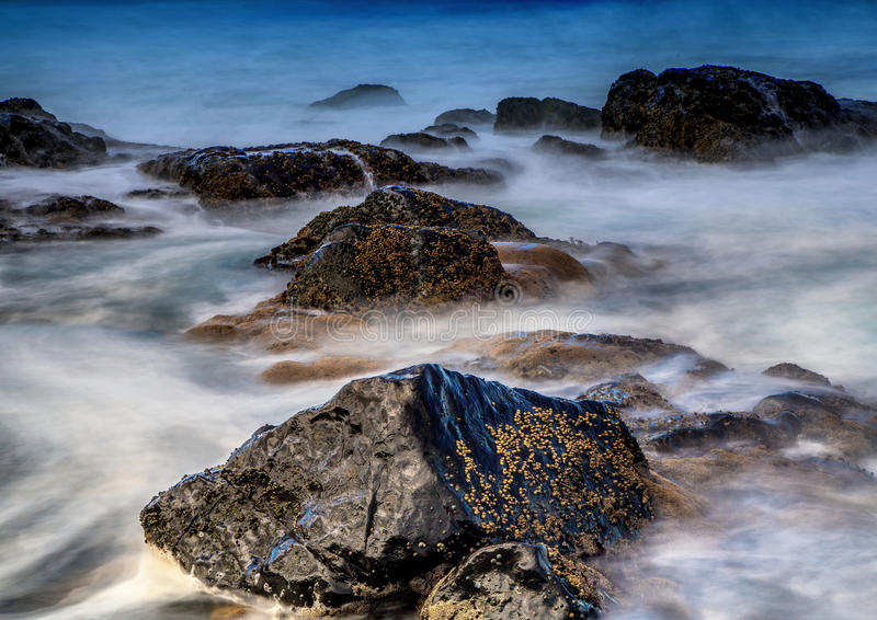Long time exposure of waves around rocks at the Wild Coast at th. E Indian Ocean in South Africa during summertime royalty free stock photos