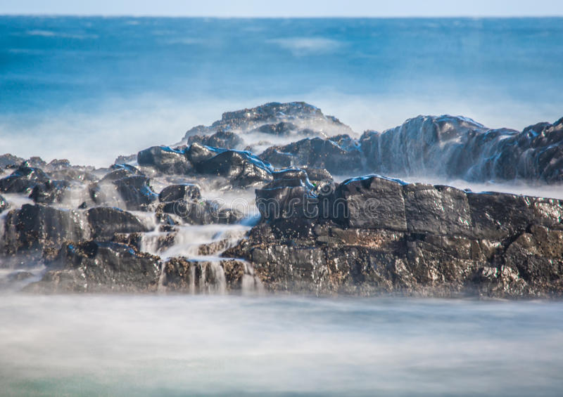 Long time exposure of waves around rocks at the Wild Coast at th. E Indian Ocean in South Africa during summertime royalty free stock images