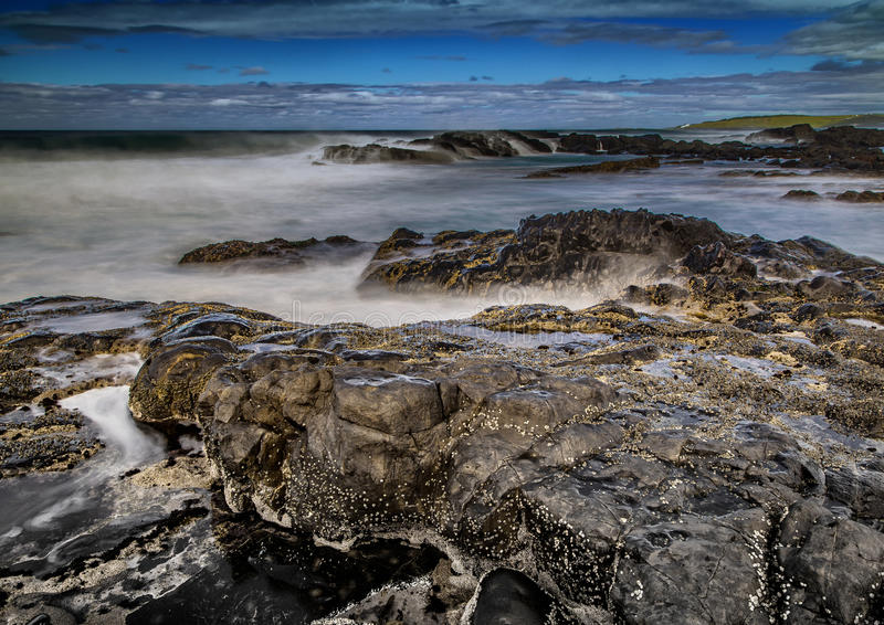 Long time exposure of waves around rocks at the Wild Coast at th. E Indian Ocean in South Africa during summertime stock image