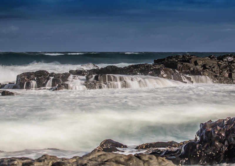 Long time exposure of waves around rocks at the Wild Coast at th. E Indian Ocean in South Africa during summertime stock photo