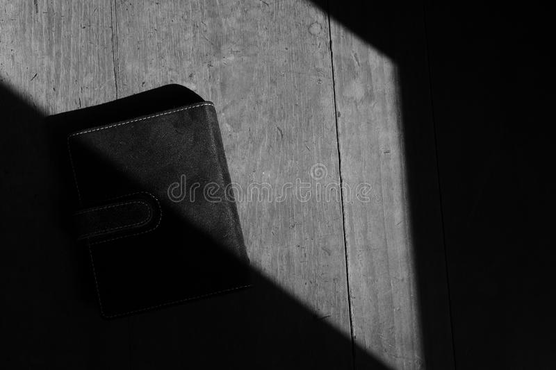 Long time secret. A black book placed on wooden surface under sunlight, black and white image stock image