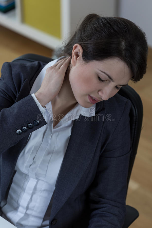 Long time at work. Woman with neck pain after long time at work royalty free stock images