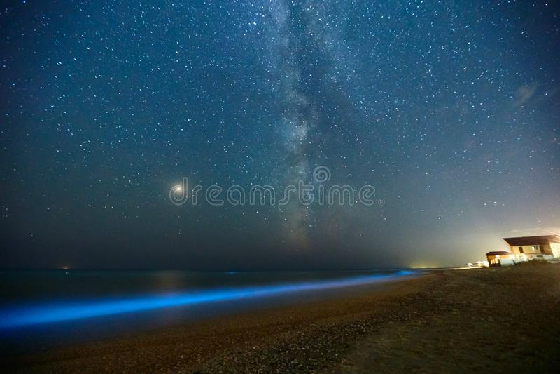 Long tir d'exposition du plancton rougeoyant sur le ressac de mer et le chemin laiteux Lueur bioluminescente bleue de l'eau sous  image libre de droits