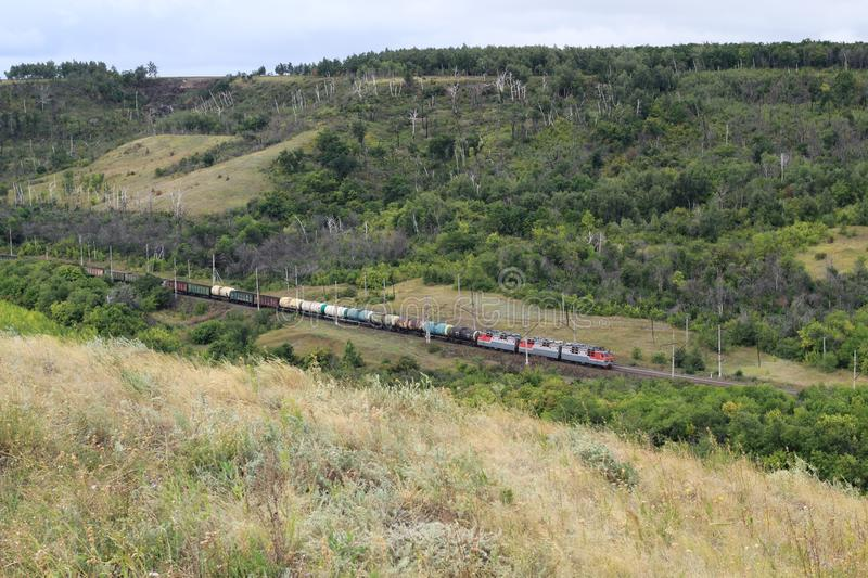 A long train loaded with double-stack cargo containers winds its way around tight s-curves in mountain countryside. All ID marks royalty free stock photo