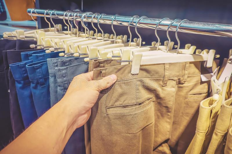 Long trousers or pants jeans clothing for sale discount in store. Man hand check some jeans and choose some item. royalty free stock photography