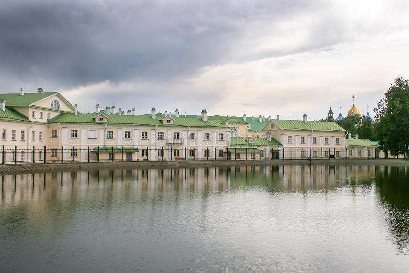 A long two-story house with a green roof, located behind a fence on the pond on an overcast day. In the distance are the domes of the Holy Trinity St. Sergius stock images