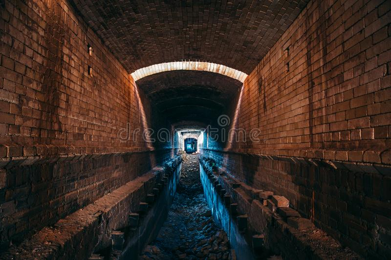 Long underground brick tunnel or industrial corridor, creepy and horror atmosphere, perspective. Toned stock photos