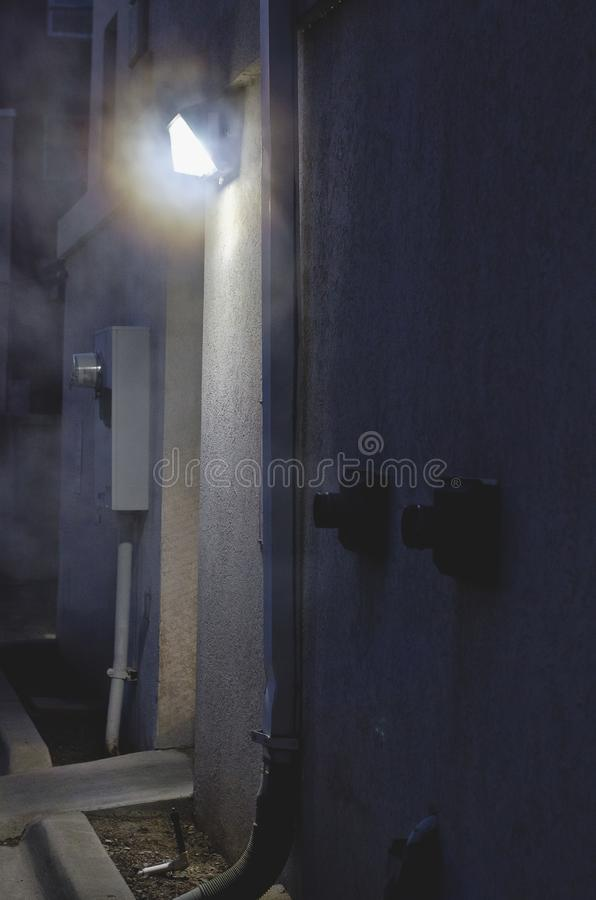 Steam in the dark alleyway. A long view of the steam on the side of the dark alleyway wall royalty free stock image