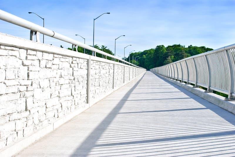 Long walking path in a modern white metal bridge stock image