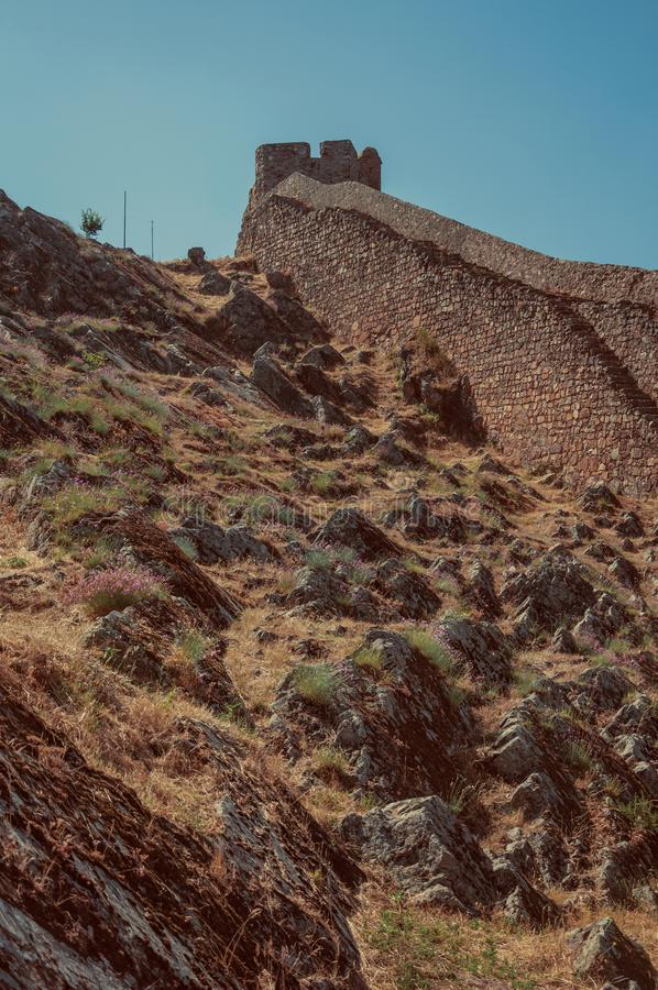 Long wall made of stone rising along the hill in Marvao. Long stone wall rising along the hill covered by rocks and dry grass, in a sunny day at Marvao. An royalty free stock images