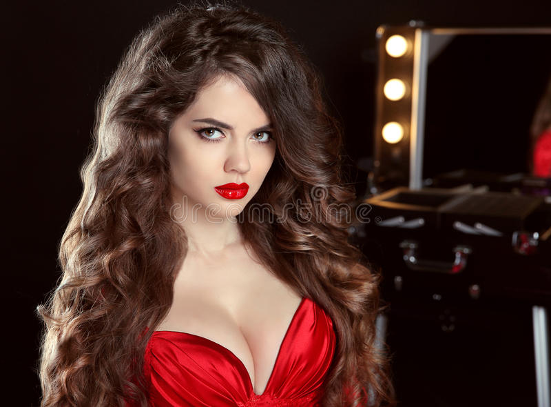 Long wavy hair. Beautiful brunette girl with red lips in sensual stock photo
