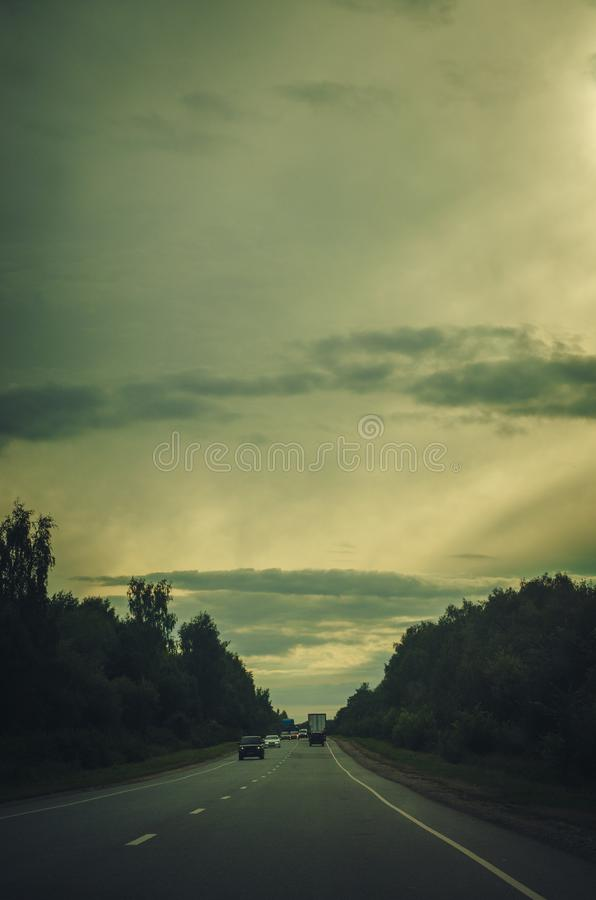Free Long Way To The Horizon On The Cloudy Evening With Road And Cars. Vintage Toned Background Royalty Free Stock Image - 155203976