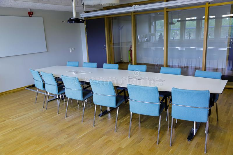 Long white office table with twelve blue chairs in the meeting room. Business concept. Modern office style stock photos