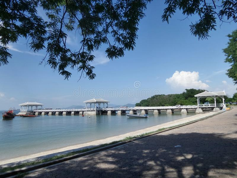 Long White outreach to the sea bridge on the remote island. Quiet beach in ceased palace area on Sichang Island , Chonburi , Thailand royalty free stock image