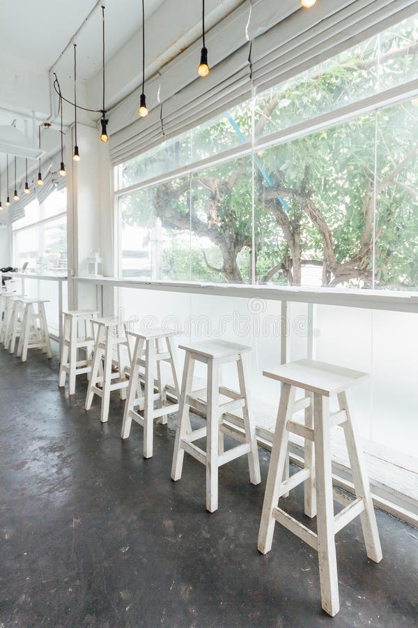 Long white wooden table and chairs with glass window and trees in background.  royalty free stock photo