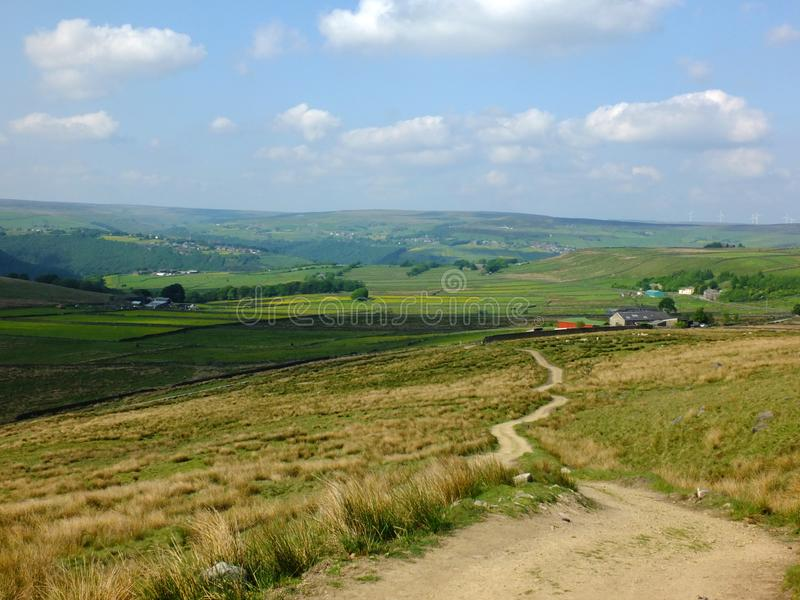 A long winding footpath running downhill in stoodley moor in yorkshire with fields and farms in the distance with pennine hills royalty free stock image