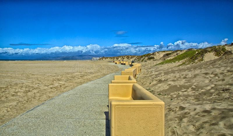 Coast path benches Oxnard California. Long winding path with tan concrete benches line the coastline in Mandalay Bay Oxnard California royalty free stock images